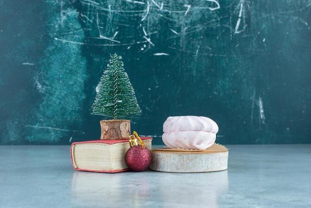 Configurazione decorativa di una pallina, una figurina di albero su un piccolo libro e biscotti impilati su marmo.
