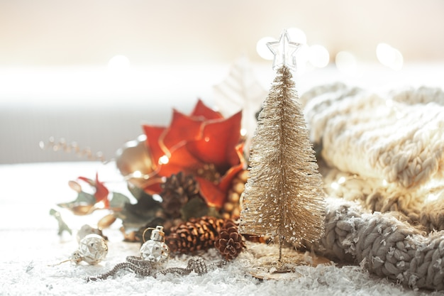 Decorative shiny christmas tree on blurred background of decor details with bokeh.