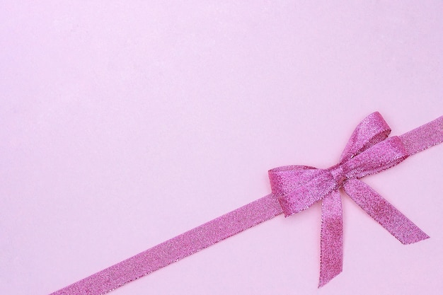 Decorative shiny ribbon with bow on pastel pink background