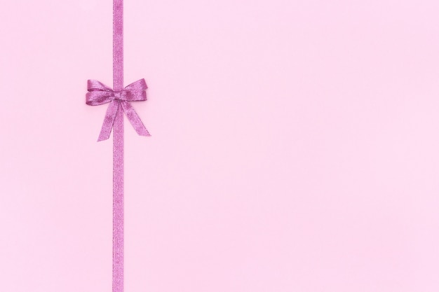 Decorative shiny ribbon with bow on pink background.