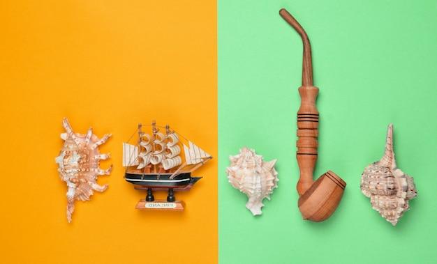 Декоративный корабль, ракушки, куриная труба на цветном пастельном фоне
