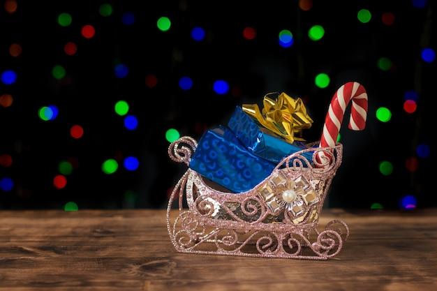 Декоративные сани с синими подарочными коробками. с рождеством