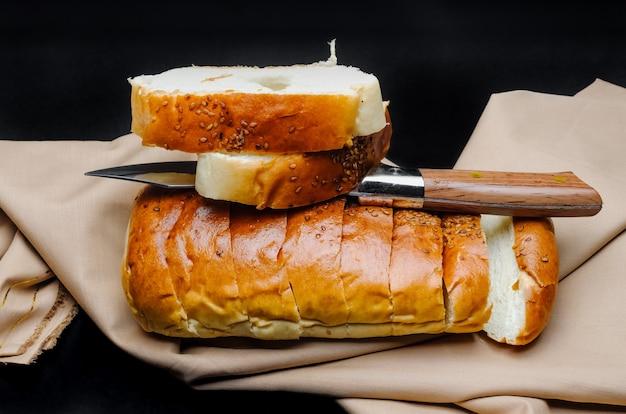 粗い暗い背景にナイフで茶色の布の上に装飾的なスライス小麦パン