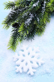 Decorative snowflake and fir tree on light background