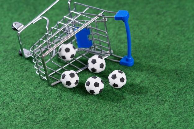 Декоративные футбольные мячи, выпавшие из тележки для покупок
