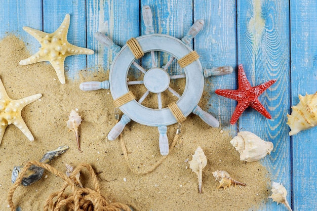 Decorative steering wheel with starfish, seashells on the sandy beach blue wood background