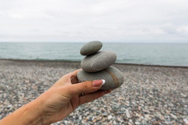 手に装飾的な石と美しい海辺。高品質の写真
