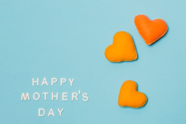 Decorative symbols of heart near happy mothers day title
