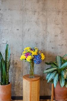 背景としてコンクリートの壁とフラワーアレンジメントと装飾的なテーブル