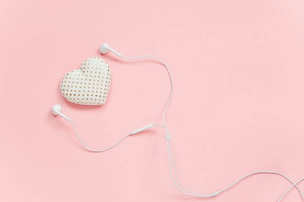 Decorative textile volume heart and white headphones on pink background. concept listen to your heart or love of music.