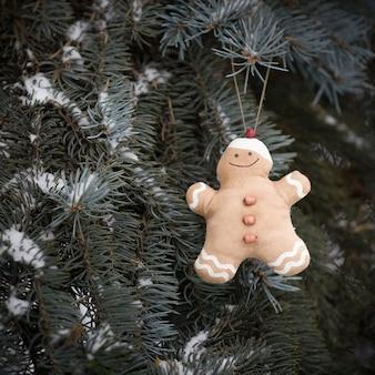 Декоративная игрушка пряничный человечек висит на живой елке в лесу