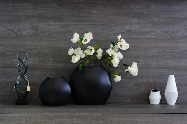 Decorative vases and flowers at dark wooden shelf