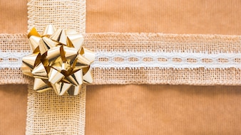 Decorative weaving ribbon and golden bow on gift paper