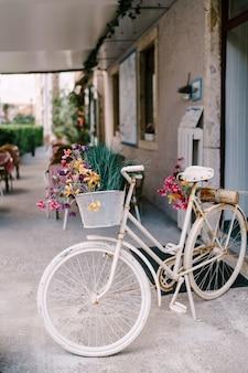 홀의 흰색 바닥에 있는 바구니에 야생화가 있는 장식용 흰색 자전거