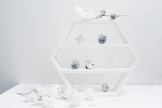 Decorative white bookcase with christmas decor. cones, cotton flowers
