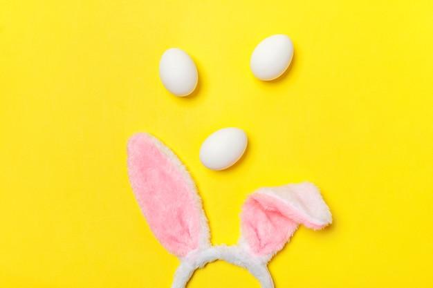 Декоративные белые яйца и кроличьи ушки пушистая костюмная игрушка, изолированные на желтом столе