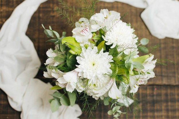 Decorative white flower bouquet with scarf on wooden table