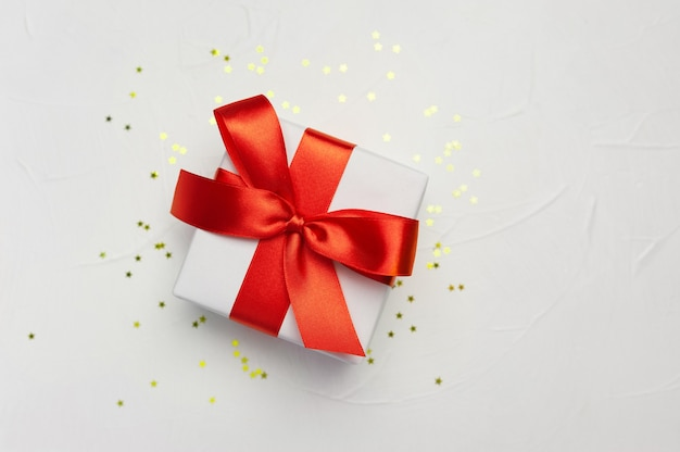 Decorative white gift box with a large red bow with golden little stars.