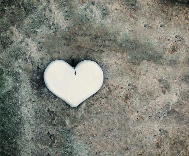 Декоративное белое сердце ручной работы на деревянных фоне.