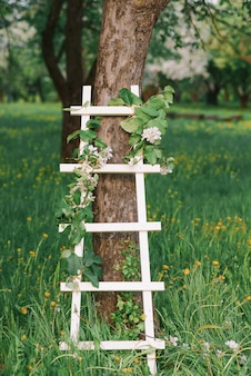 Decorative white stepladder in a blooming garden in spring. romantic decor