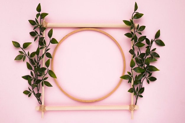 Decorative wooden empty frame with leaves on pink wall