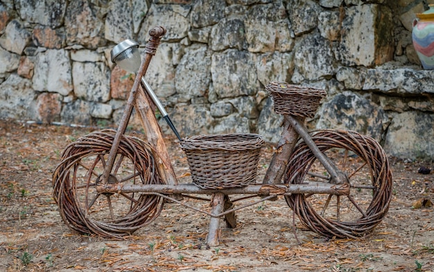 Decorative wooden handmade brown bike outdoors stone wall