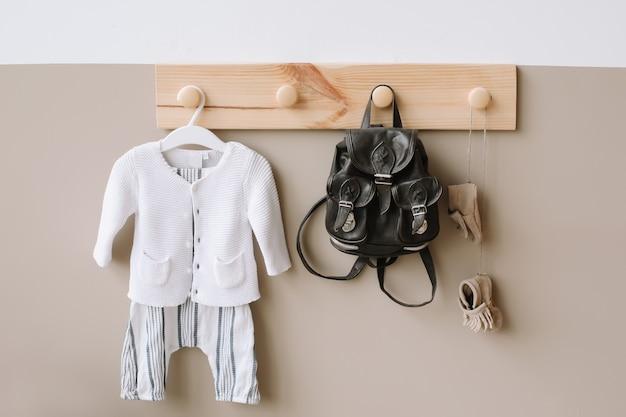 白と茶色の壁にバッグと子供用ニット衣装の装飾的な木製ハンガー