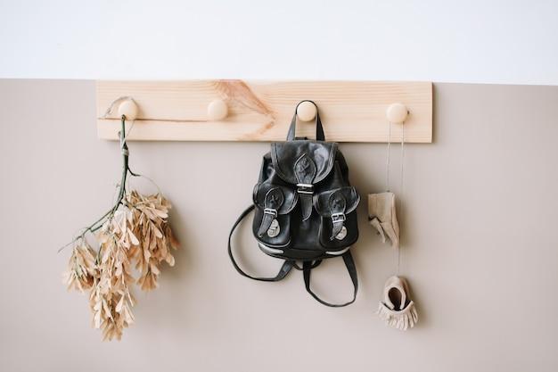 子供のインテリアのディテールとして白と茶色の壁にバッグが付いた装飾的な木製ハンガー