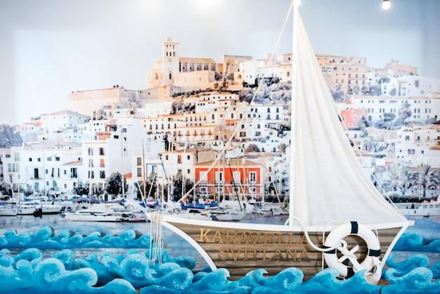 Jacht di legno decorativo si trova prima di una foto di porto marino sulla parete