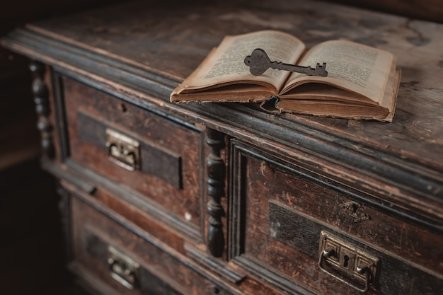 A decorative wooden key rests on an open old vintage book