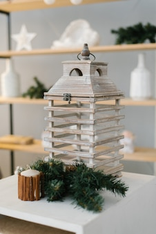 Decorative wooden lantern with sprigs of christmas tree next to home interior decor