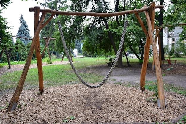 Декоративные деревянные качели из толстой веревки на одно место на фоне летнего парка