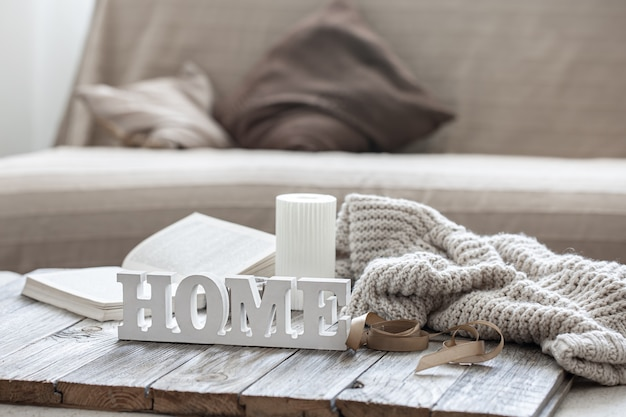 Decorative wooden word home, book, candle and knitted element on blurred background.