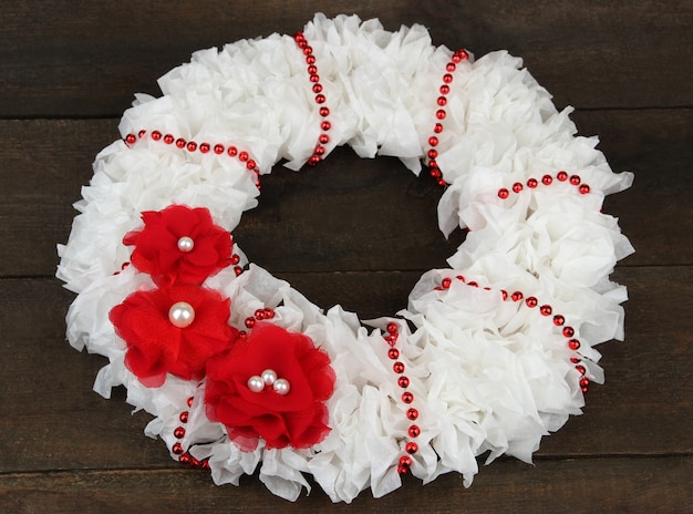 Decorative wreath with flowers on wooden background