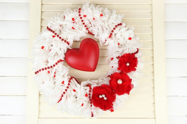 Декоративный венок с сердцем на деревянном фоне