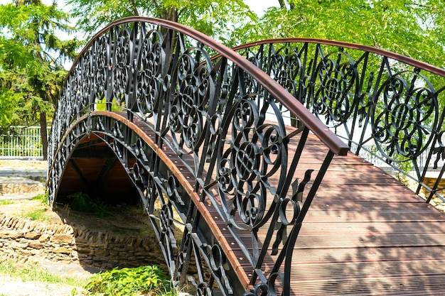 Decorative wrought iron wooden bridge over the river of stones in the park.