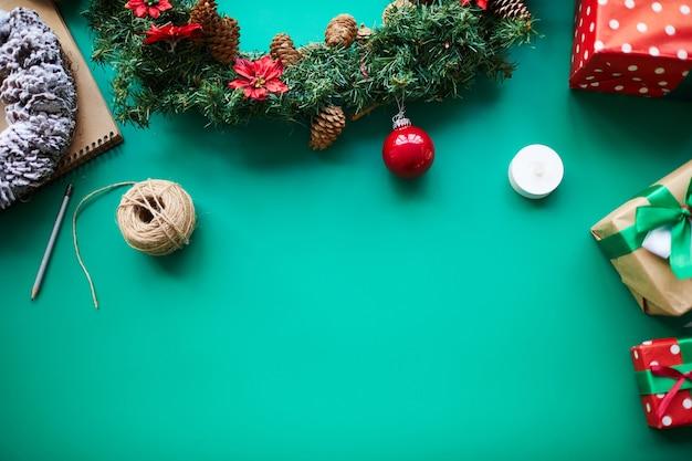Декоративные рождественские вещи и подарки на зеленом фоне
