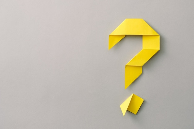 Decorative yellow paper origami question mark on grey with copy space for use as a design template