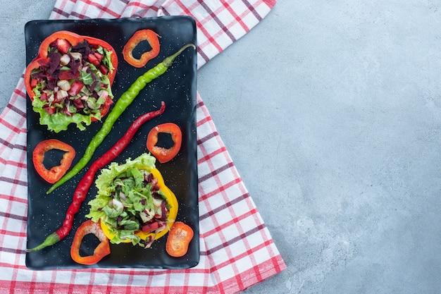 얇게 썬 피망과 대리석 위에 칠리 페퍼로 장식 된 플래터에 장식 적으로 정렬 된 샐러드 부분.