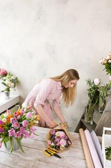 포장지에 장식 팩 축제 꽃다발. 젊은 아름 다운 플로리스트는 플로리스트 리가 나무 배경에 워크샵에서 분홍색 모란과 야생화로 조립하게합니다. 직장에서 여자
