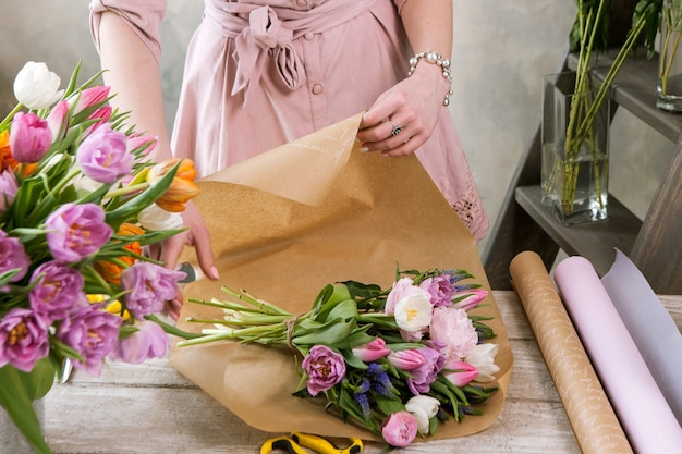 포장지에 장식 팩 축제 꽃다발. 젊은 아름 다운 플로리스트는 플로리스트 리가 나무 배경에 워크샵에서 분홍색 모란과 야생화로 조립하게합니다. 직장에서 여자의 손