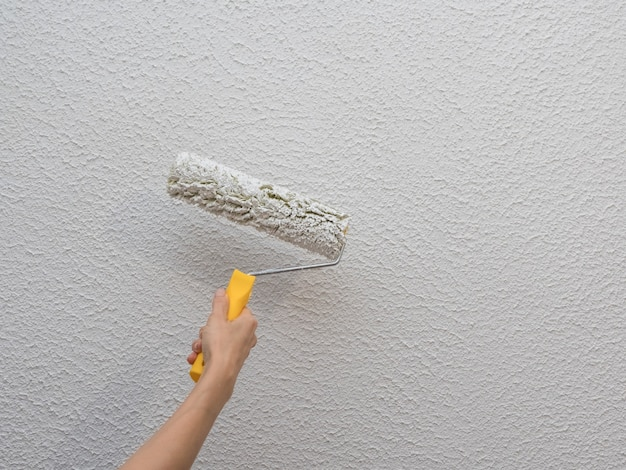 Decorator's hand painting white wall with roller.