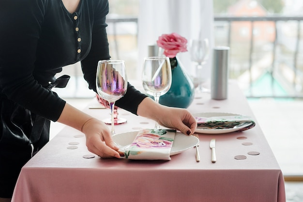 Decorator serving party table in gentle pink colors with pink tablecloth, white dishes, glasses for wine, floral napkin. happy birthday or baby shower for girl.