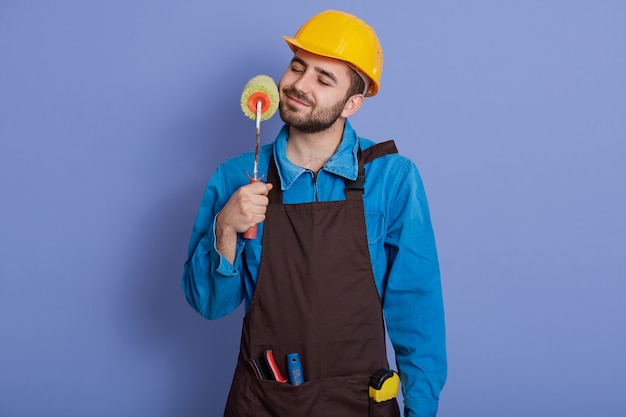 Decorator with paint roller in hands touching his beard and keeps eyes closed, guy wearing helmet and brown apron