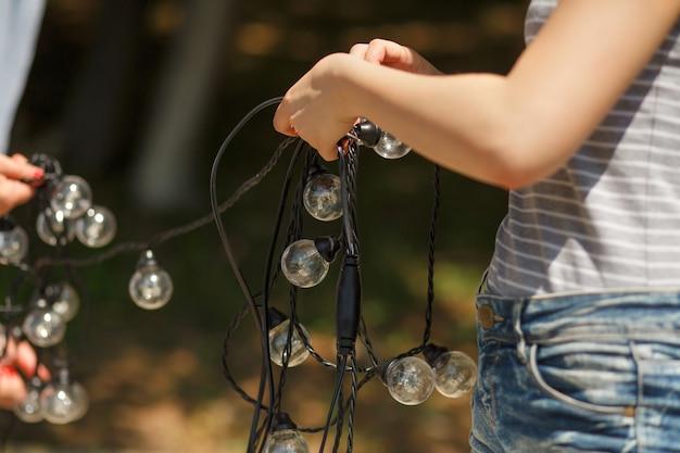 Decorators prepare and unravel black wires of bulb lamp garland