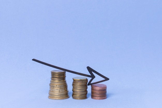 Уменьшение стопки монетных денег со стрелкой
