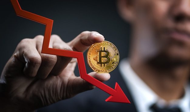 Decreasing value of bitcoin. businessman holding bitcoin with red 3d arrow down