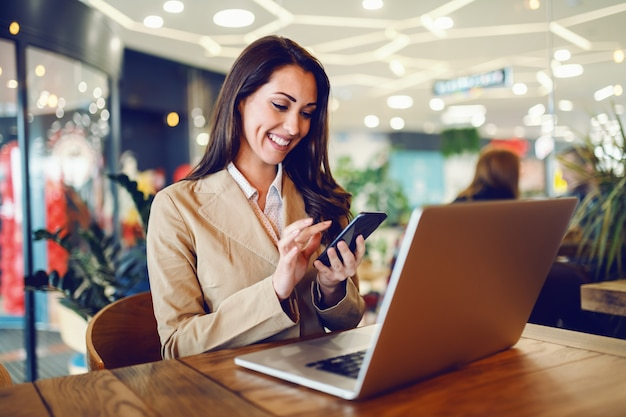 Dedicated attractive caucasian businesswoman dressed in beige jacket using smart phone while sitting in cafe. on table is laptop.