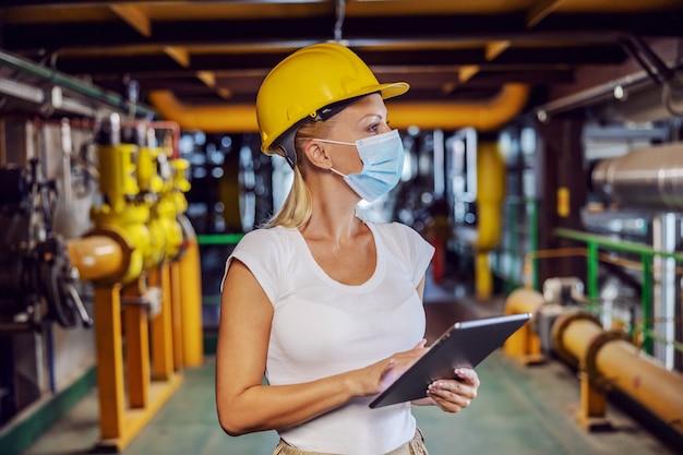 Преданная белокурая женщина-работница в рабочей форме со шлемом на голове и в защитной маске стоит на теплофикационной станции и использует планшет во время вируса короны. женщина делает мужскую работу концепции.