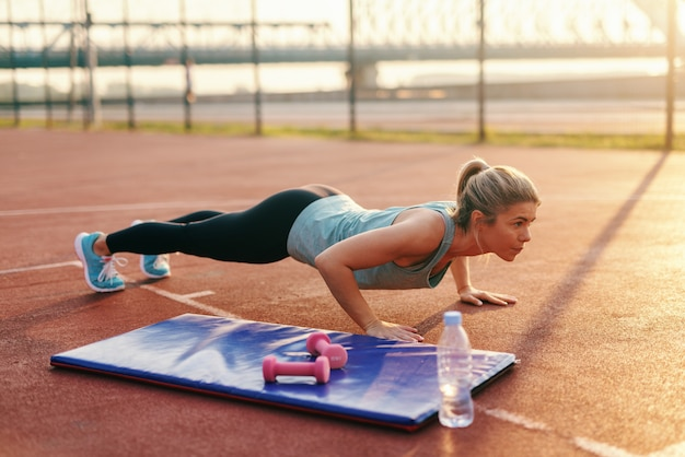 ポニーテールと朝のコートで腕立て伏せを行うスポーツウェアに身を包んだ熱心なブロンドの女性。